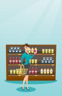 Femme tenant un panier et une bouteille de sauce.