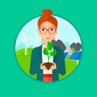 Femme tenant une petite plante verte.