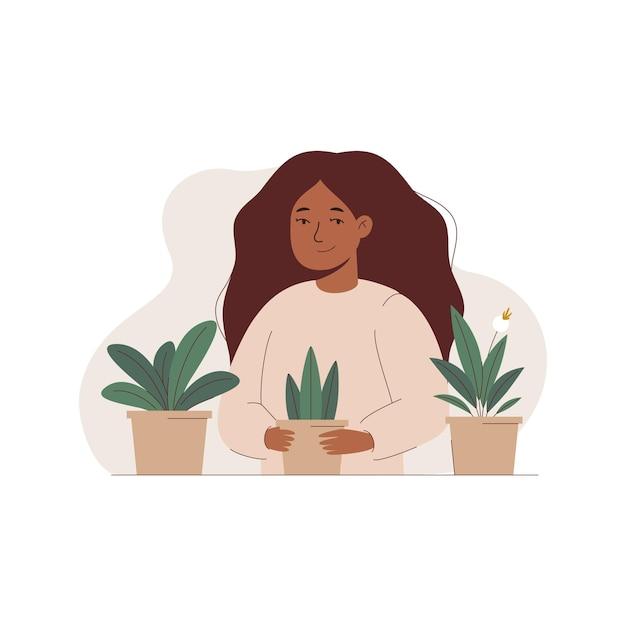 Femme tenant un pot de fleur avec une plante dans ses mains