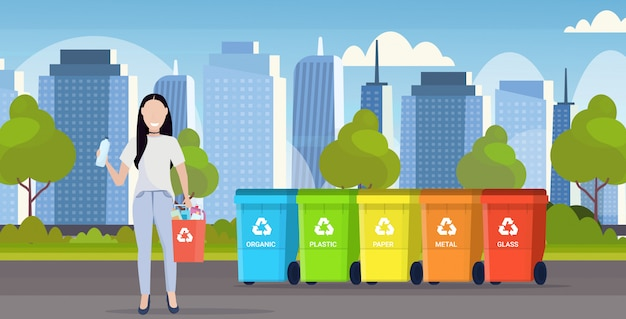 Femme tenant un seau avec des déchets en plastique près de conteneurs différents types de bacs de recyclage séparent le concept de gestion du tri des déchets paysage urbain moderne fond plat horizontal pleine longueur
