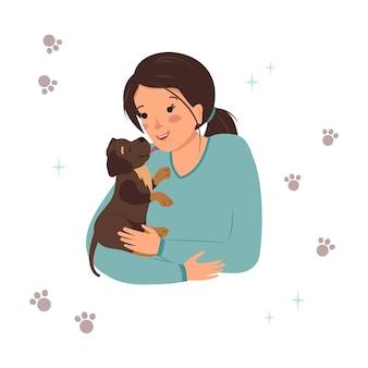 Une femme tient un chiot labrador retriever dans ses bras