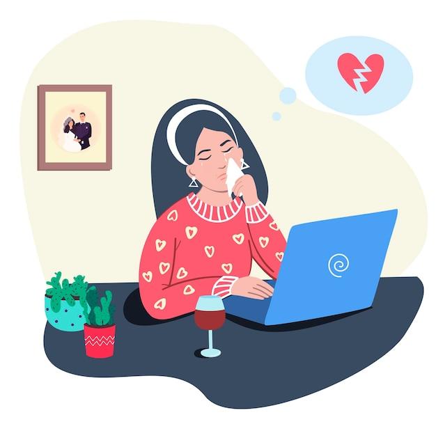 Femme triste avec le coeur brisé devant l'ordinateur
