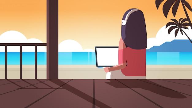 Femme, utilisation, ordinateur portable, exotique, mer, plage, vacances été, communication en ligne, blogging, concept, vue postérieure, blogger, séance, sur, terrasse bois, paysage marin