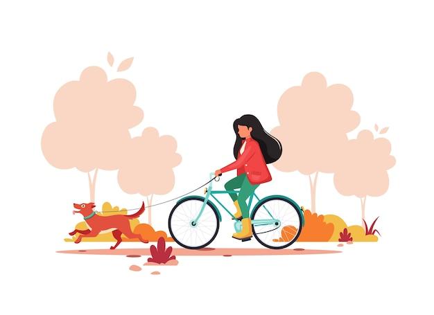 Femme à vélo avec chien en automne parc. concept d'activité de plein air.