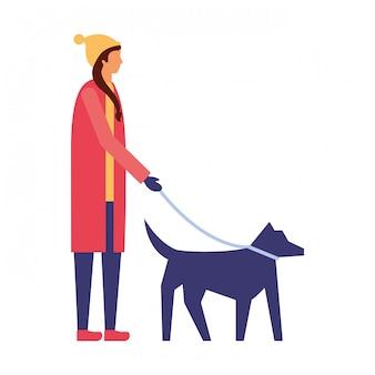 Femme avec des vêtements d'hiver promener son chien