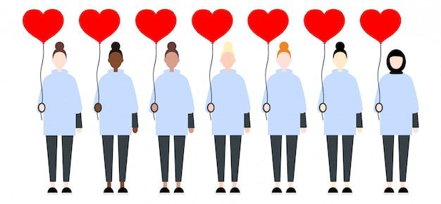 Femmes dans des vêtements décontractés, tenant des coeurs de ballon rouge