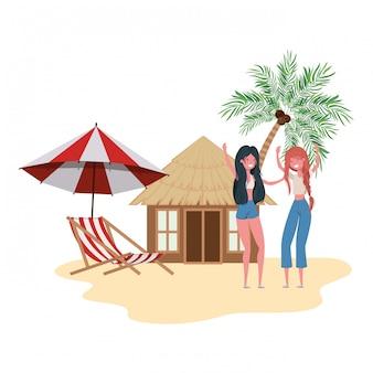 Femmes debout dans la plage avec maison de plage