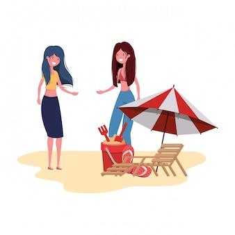 Femmes debout sur la plage avec parasol