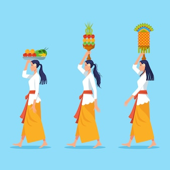 Les femmes qui marchent à bali portent des offrandes pour le rituel de purification