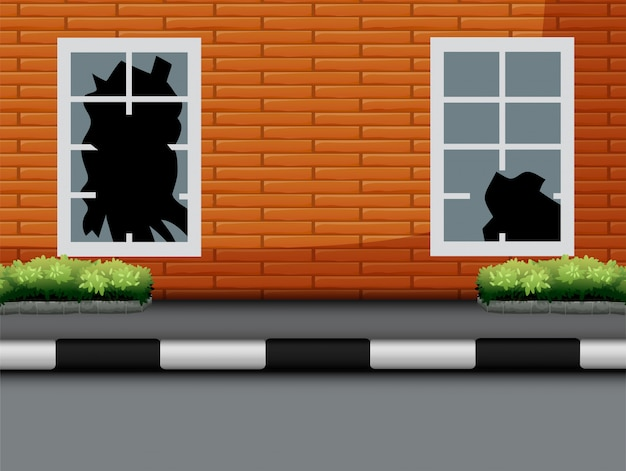 Fenêtre avec verre brisé sur mur de briques rouges