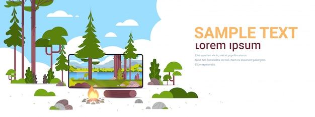 Feu de camp dans la forêt sauvage d'été belle rivière montagnes paysage nature tourisme camping ou randonnée concept écran smartphone application mobile en ligne