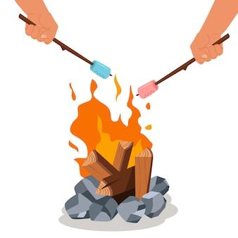 Feu de camp et griller la guimauve sur le bâton dans les mains