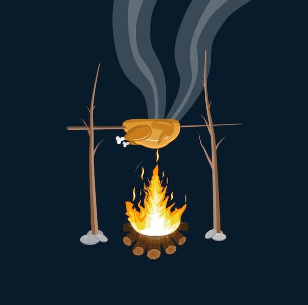Feu de joie avec du poulet grillé. bûches et feu.