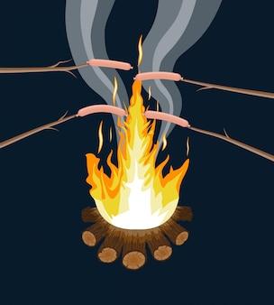 Feu de joie avec des saucisses grillées. bûches et feu.