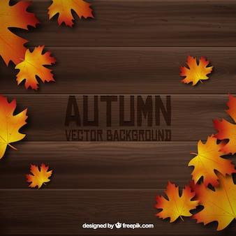 Feuilles d'automne réalistes sur une planche de bois