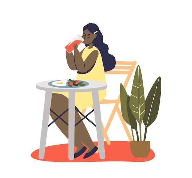 Fille d'âge préscolaire mangeant des œufs et des légumes, buvant du jus pour le petit déjeuner. un enfant heureux savoure un repas savoureux