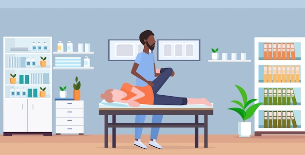 Fille allongée sur un lit de massage masseur thérapeute faisant un traitement de guérison massage des jambes du patient manuel de physiothérapie sport concept cabinet médical clinique intérieur pleine longueur