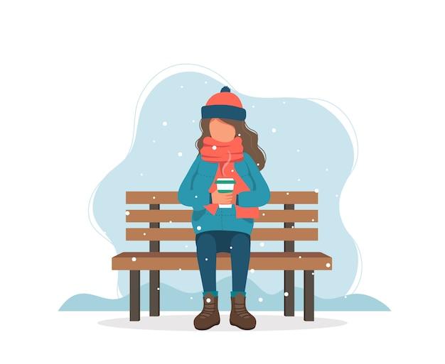 Fille assise sur un banc en hiver avec un café.