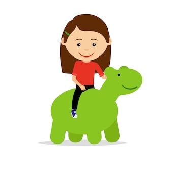 Fille assise sur un jouet de dinosaure vert