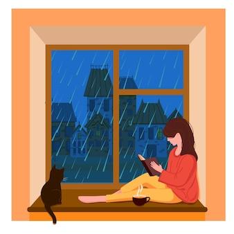 Une fille assise près de la fenêtre lit un livre