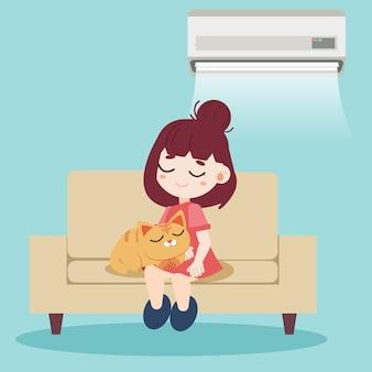 Une fille et un chat mignon assis ensemble sur le canapé