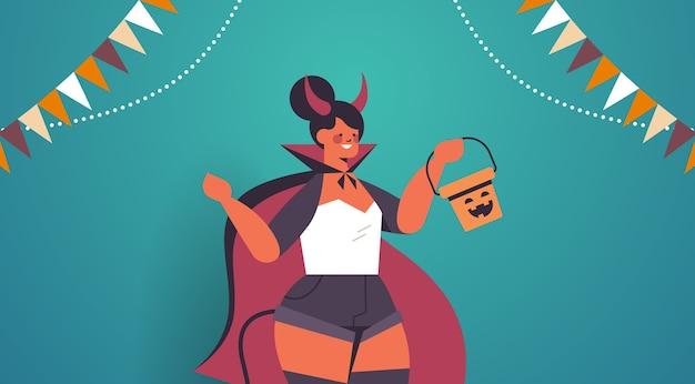 Fille en costume de diable tenant seau avec citrouille heureux halloween vacances célébration concept portrait illustration vectorielle horizontale