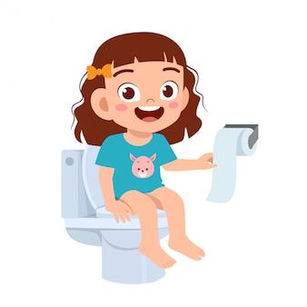 Fille enfant mignon heureux assis sur les toilettes