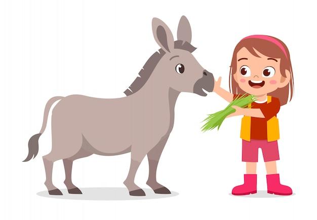 Fille enfant mignon heureux nourrissant un âne mignon