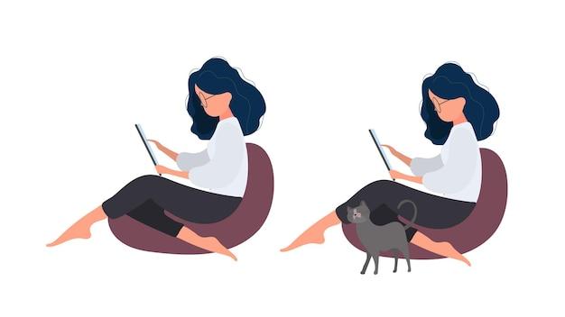 La fille est assise sur un pouf et travaille à la tablette. une femme avec une tablette est assise sur un grand pouf. le chat se frotte contre la jambe de la fille. vecteur.