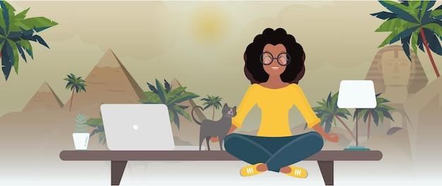La fille est assise à la table du bureau et rêve d'egypte. bureau avec vue sur le désert.