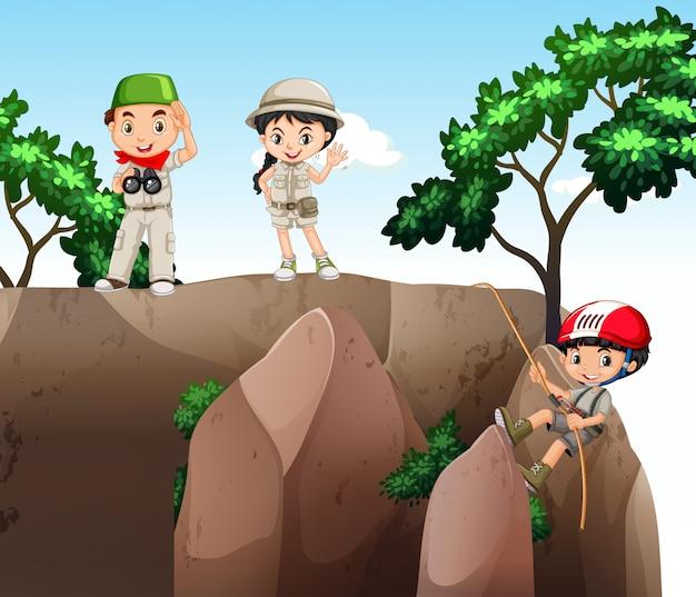 Fille et garçons grimpant dans la montagne