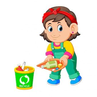 Une fille garde son environnement propre par le muguet dans une poubelle