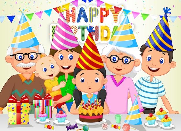 Fille heureuse soufflant des bougies d'anniversaire avec sa famille
