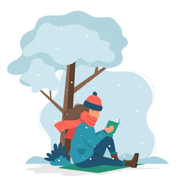 Fille lisant un livre en hiver.