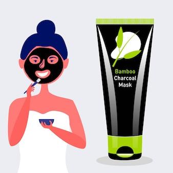 La fille met le masque de visage de brosse en bambou de charbon de bois masque de charbon de bois cosmétique noir
