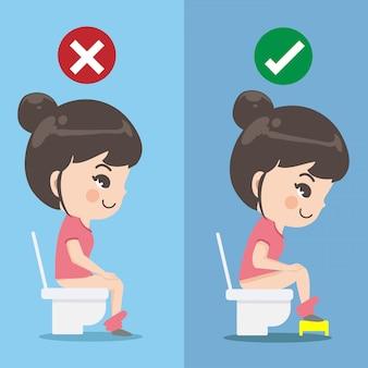 La fille montre comment s'asseoir correctement dans le siège des toilettes.