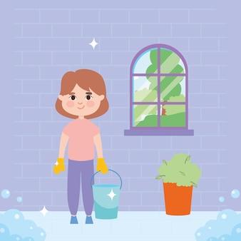 Fille avec le nettoyage du seau devant la fenêtre