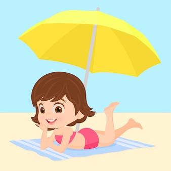 Fille sur la plage sous un parasol