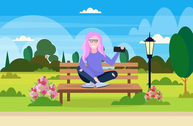 Fille prenant selfie photo sur smartphone appareil photo femme assise banc en bois en plein air parc paysage fond personnage de dessin animé féminin pleine longueur illustration vectorielle horizontale