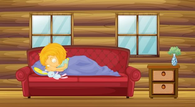 Une fille qui dort sur le canapé avec un jouet
