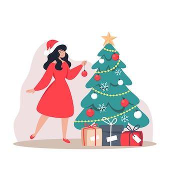 Fille en robe rouge décore l'arbre de noël