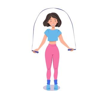 Une fille tonique fait des exercices avec une corde à sauter en tenue de sport