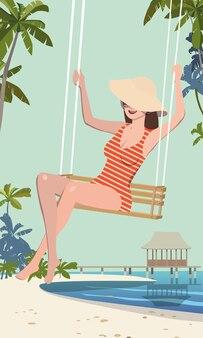 La fille va faire un tour sur une balançoire en vacances, sur la plage.