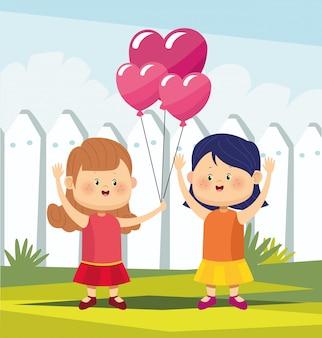 Filles mignonnes et heureuses avec des ballons coeur sur une clôture blanche