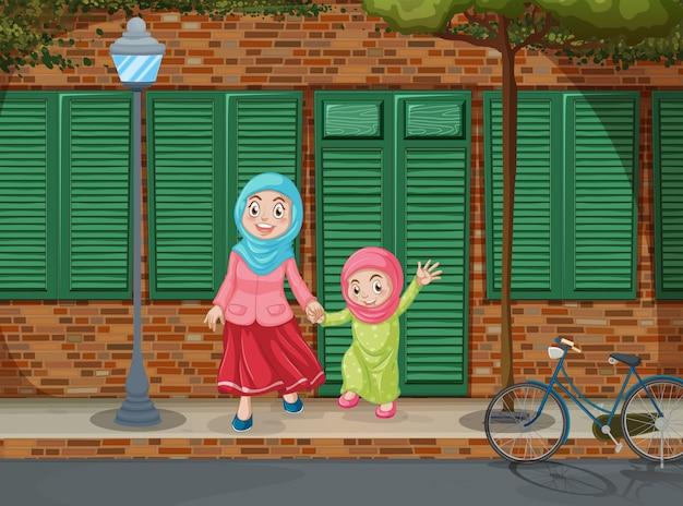 Filles musulmanes tenant par la main sur le trottoir