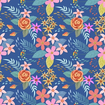 Fleurs colorées dessinées à la main sur le motif sans soudure de fond bleu.