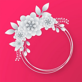 Fleurs de papier blanc avec cadre circulaire sur fond rose.