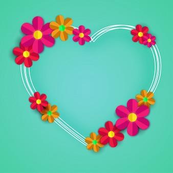 Fleurs en papier colorées avec cadre en forme de cœur sur fond vert.