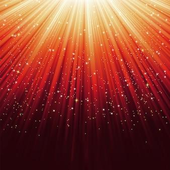 Flocons de neige et étoiles sur lumière orange.