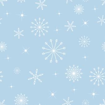 Flocons de neige modèle sans couture dans différentes tailles sur le bleu